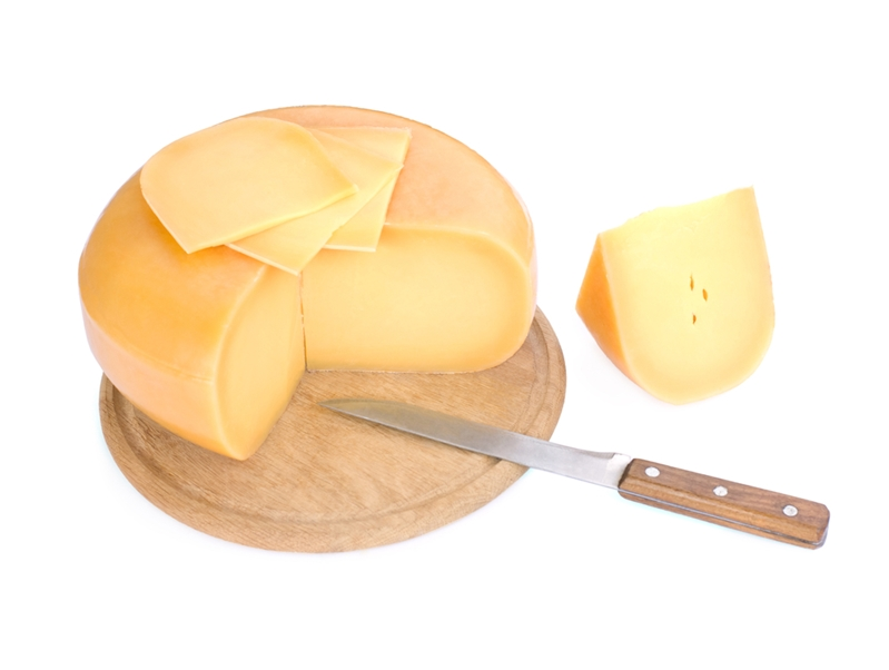 Block of cheese on cutting board sliced with knife.