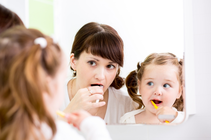 Mom and baby brushing teeth together in bathroom mirror.