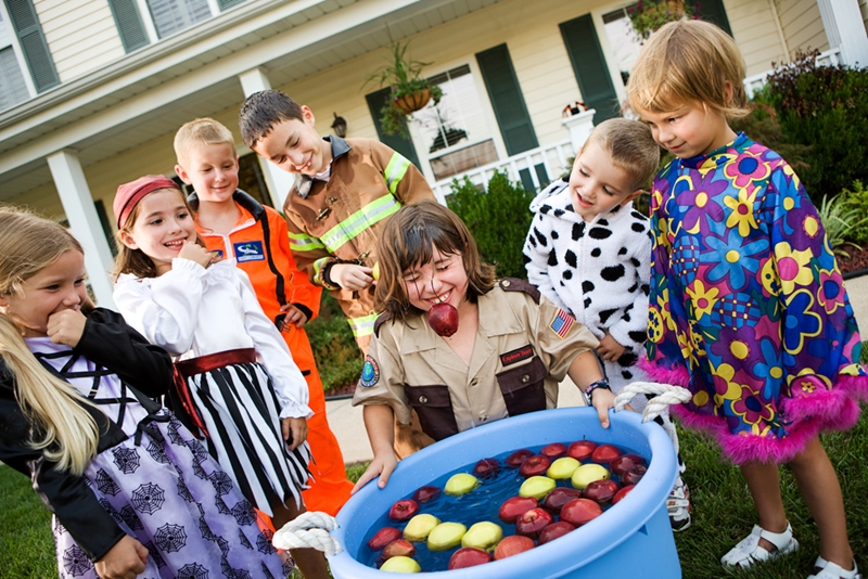 Little girl bobbing for apples at Halloween party.