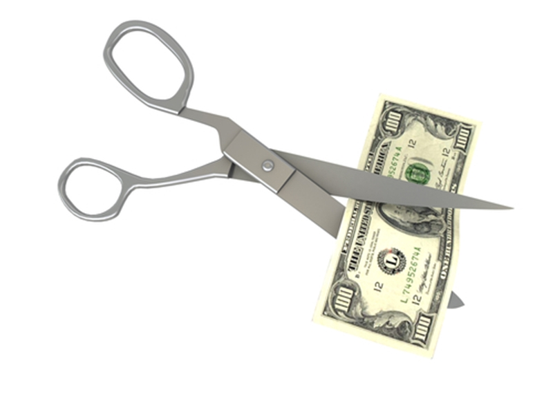 Scissors cutting $100 bill.
