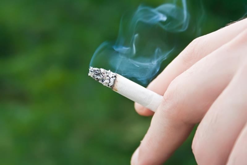 Lit cigarette emitting smoke between man's fingers.
