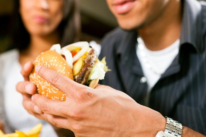 Man about to take bite of cheeseburger.