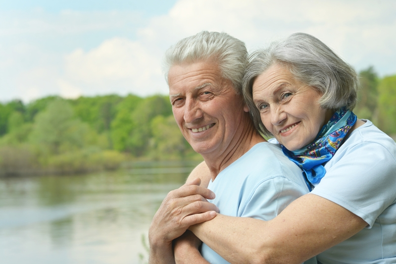Senior couple smiling and hugging.