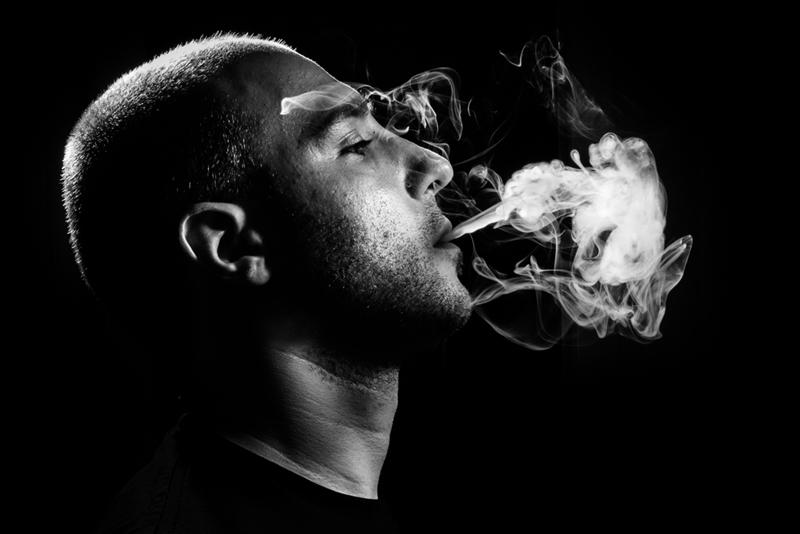 Man blowing smoke puff.