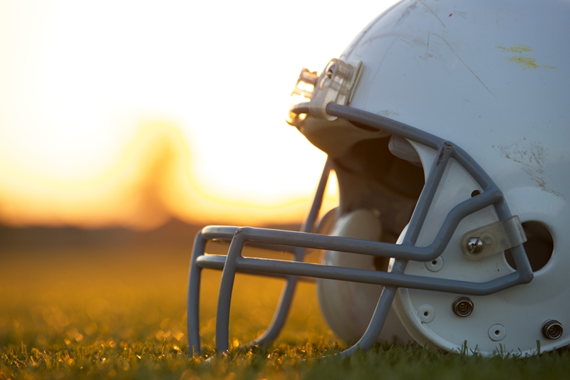 Football helmet sitting on grass with sunset background.