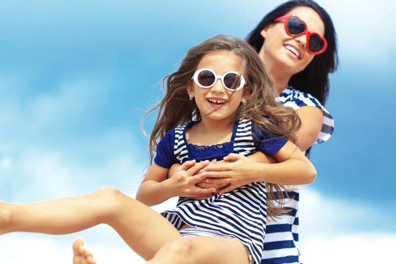 Mom swinging daughter around wearing sunglasses.