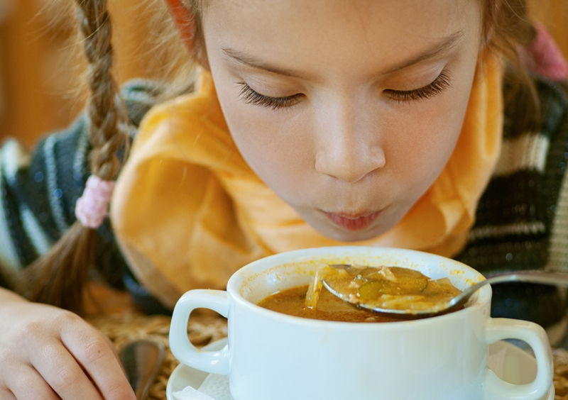 Girl blowing on spoonful of hot soup.