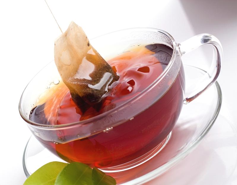Tea bag dipped in cup of red tea.