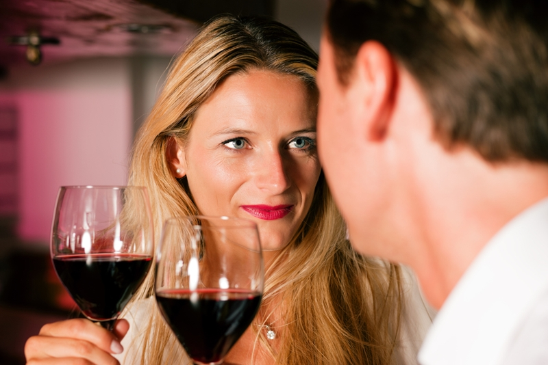 Couple on date drinking red wine.