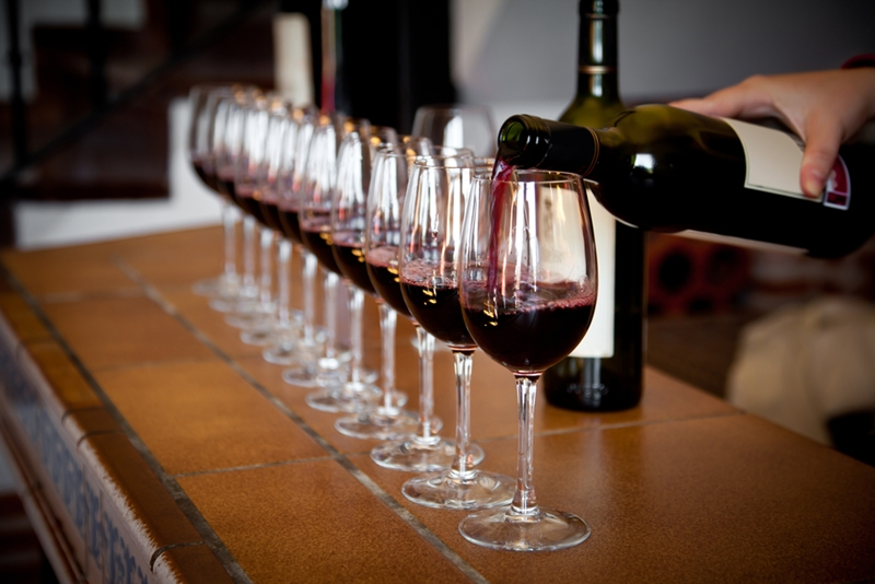 Pouring bottle of red wine into line of glasses on bar.