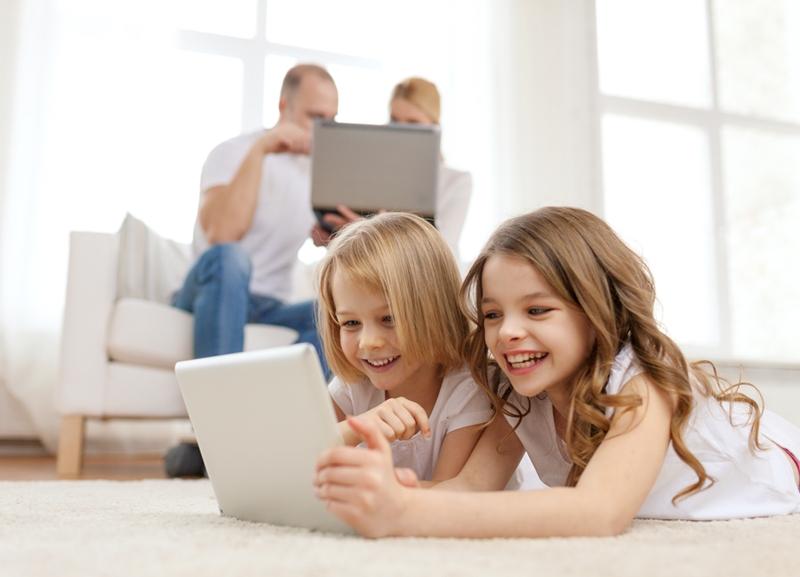 Kids smiling around computer.