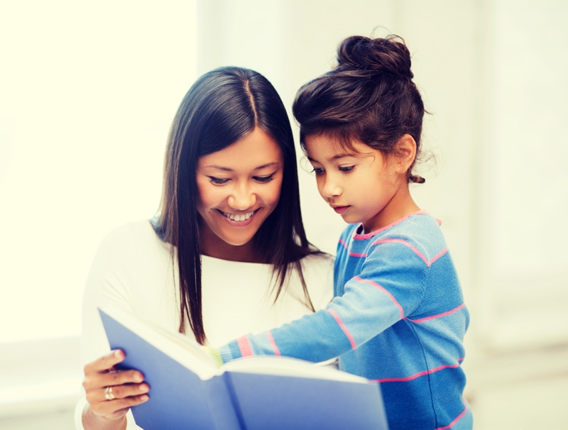 Mom and daughter reading book.