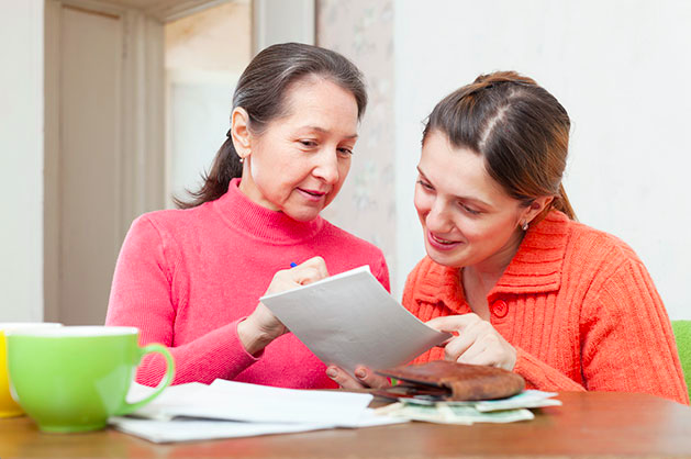 Senior Dental Health - Adult mother and daughter reviewing billing statement
