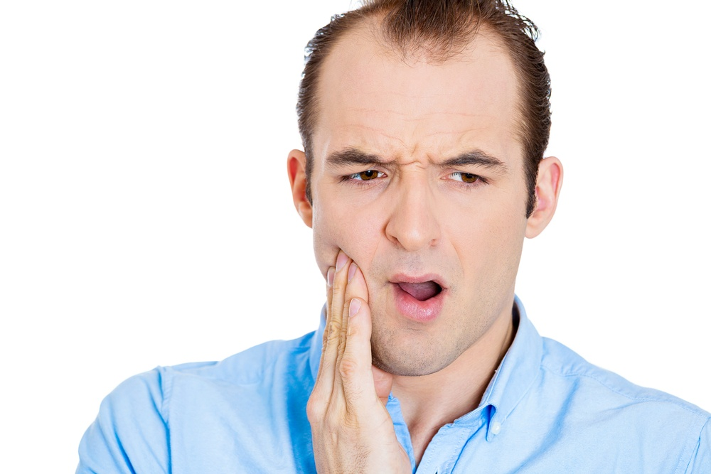 Young man with sensitive tooth ache problem