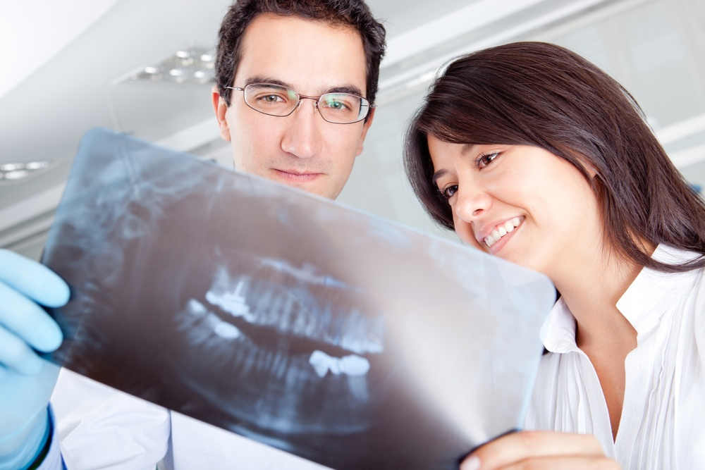 Dentist looking at an x-ray before dental implant surgery