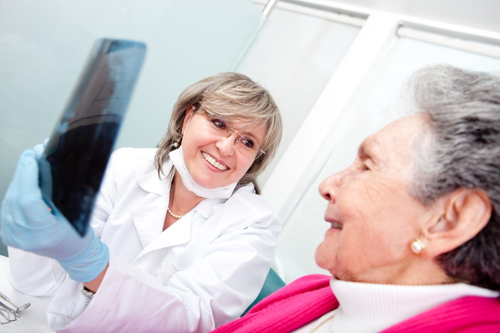 Dentist with an elder female patient looking at an x-ray