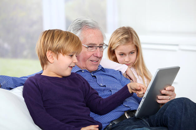 How grandparents can stay connected with grandchildren | Grandfather with kids using electronic tab