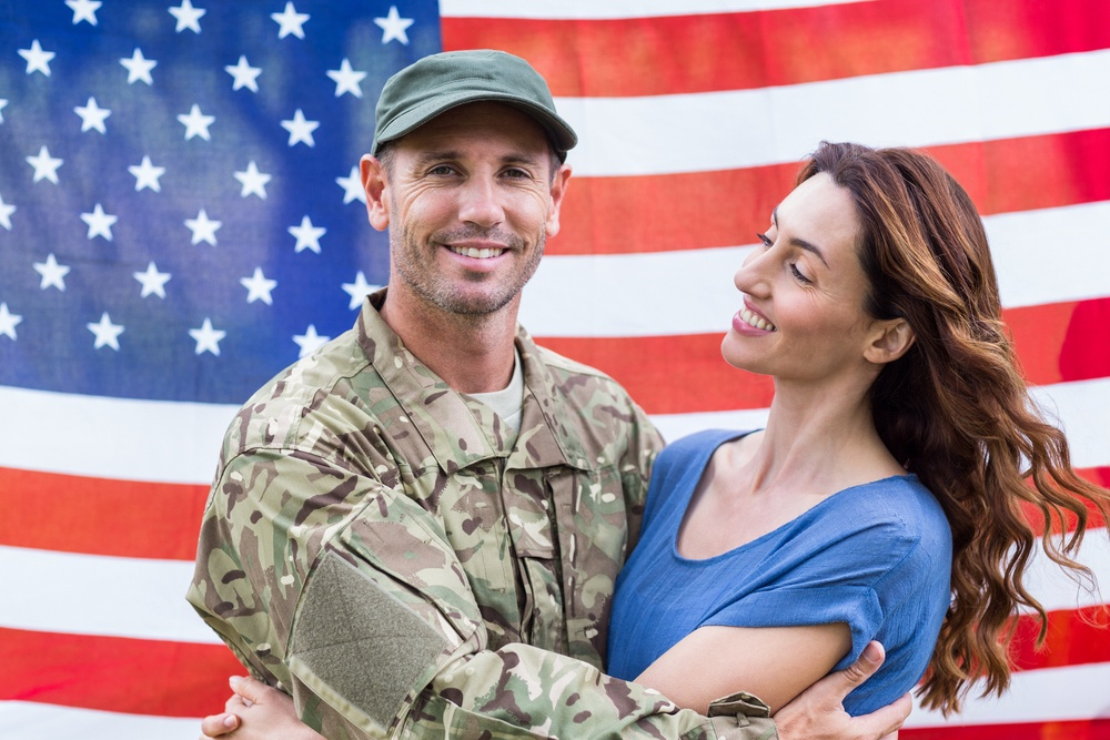 Soldier with partner smiling with American flag in the background