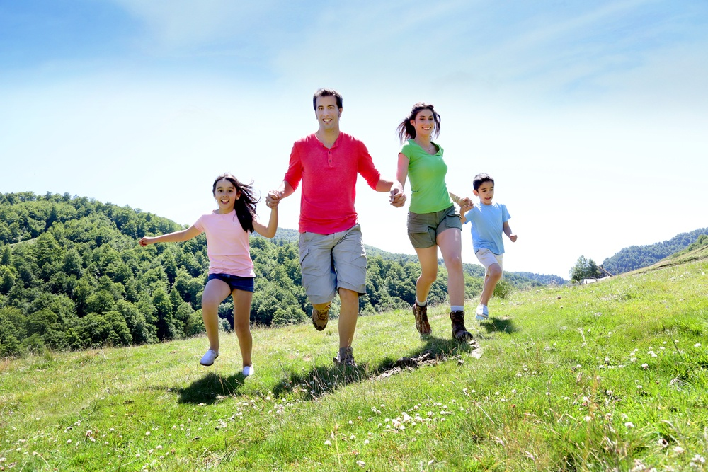 Happy family enjoying and running together in the mountains