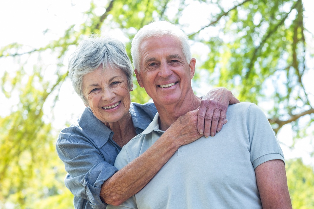Happy old couple smiling in a park
