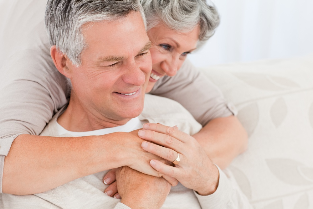 Woman hugging her husband at home and smiling