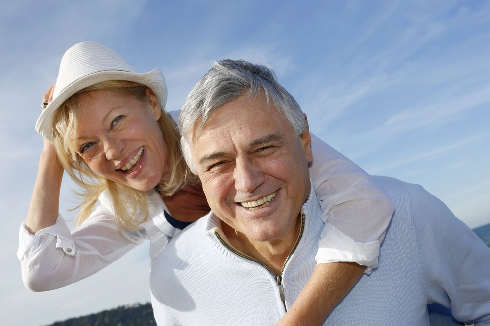 Cheerful senior couple having fun at the beach and smiling