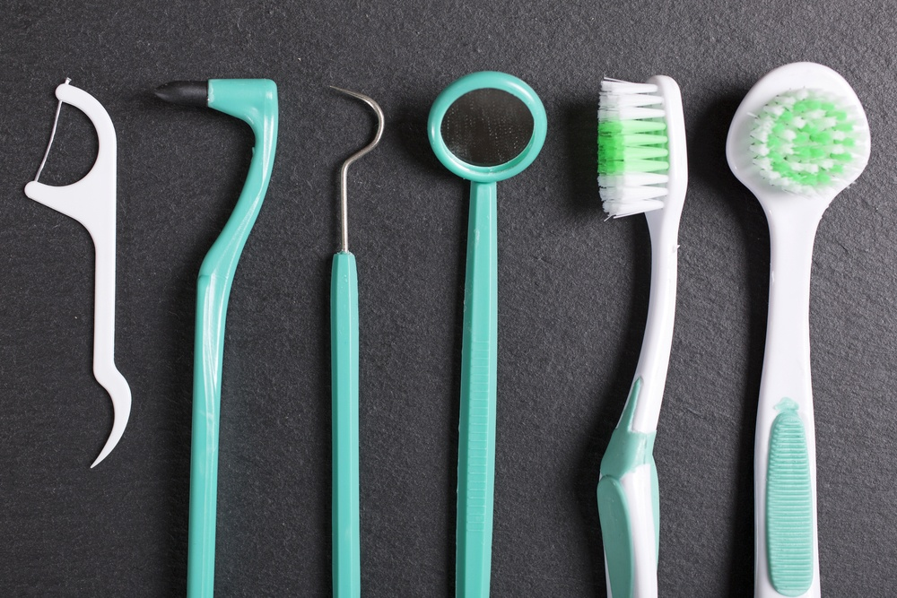 Selection of dentist brushes and tools on a black slate surface-2