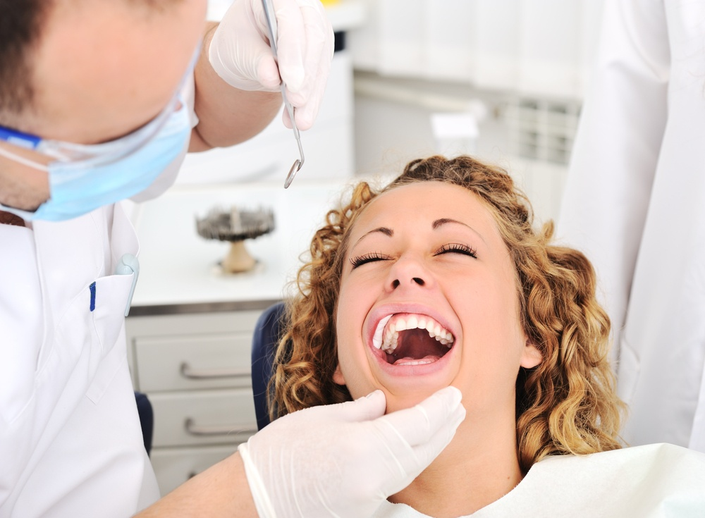 Overcoming fear of the dentist - Happy woman smiling while a dentist checks her teeth