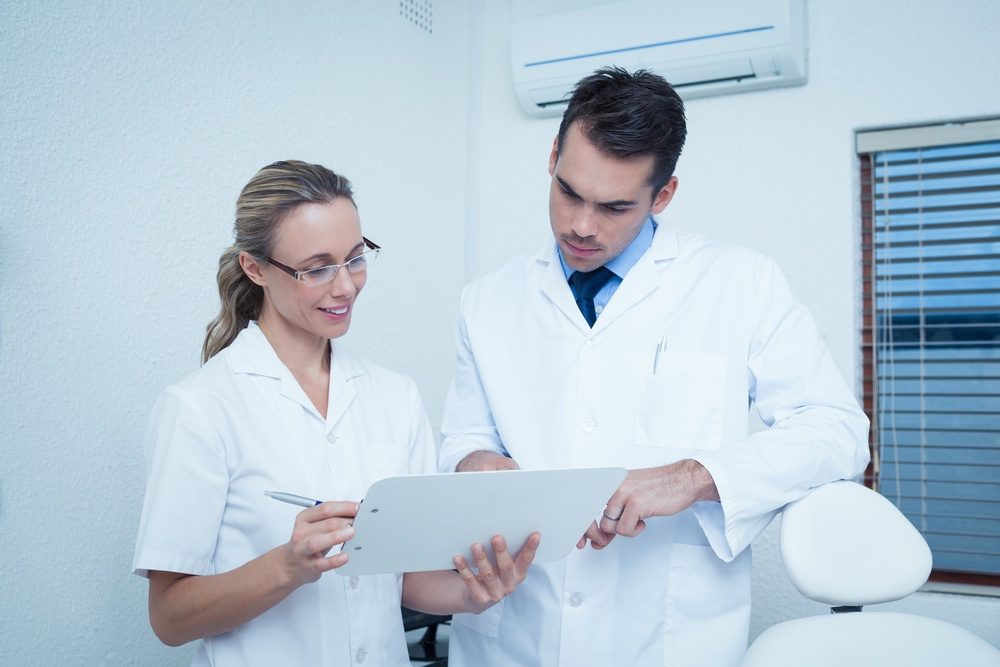 View of female and male dentists discussing reports