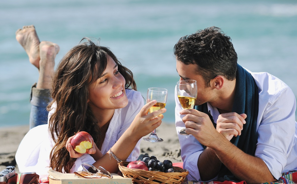 Young couple enjoying  picnic on the beach and drinking alcohol