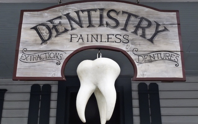 Giant wisdom tooth hanging from vintage dentist sign