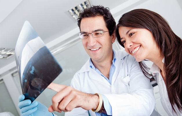 Dentist looking at an x-ray with a patient
