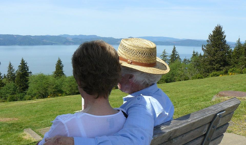Senior Dental Health - Elderly couple on bench looking at a lake