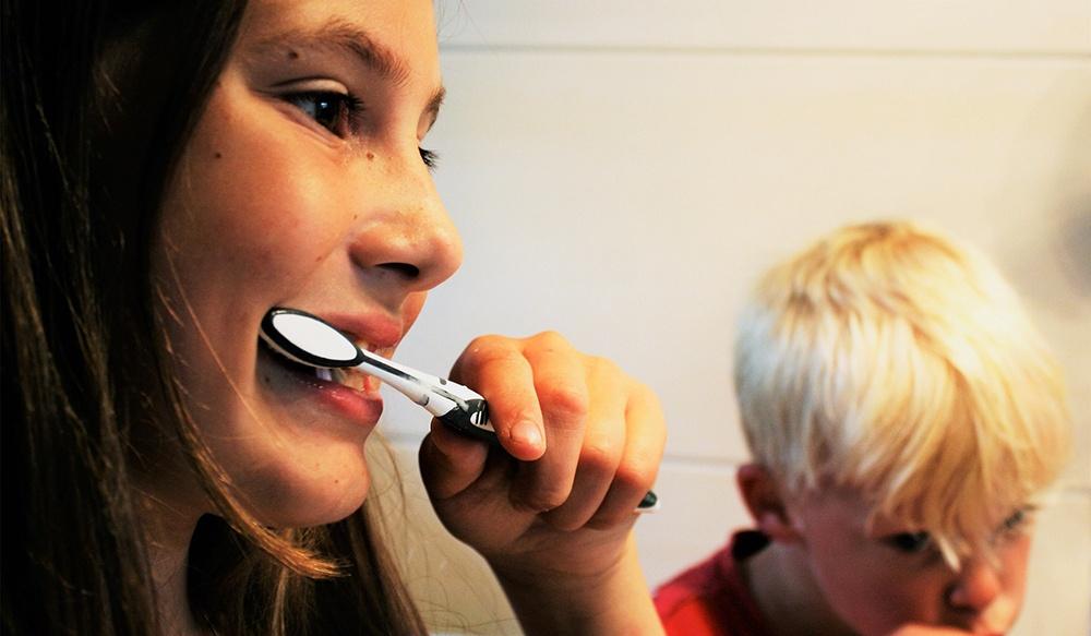 Two children brushing teeth before school