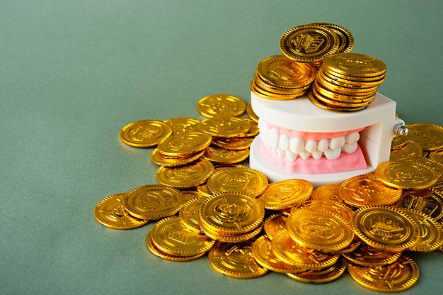 Affordable dental care - Dental teeth model and gold coins