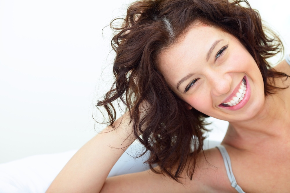 Beautiful woman lying on the sofa and laughing